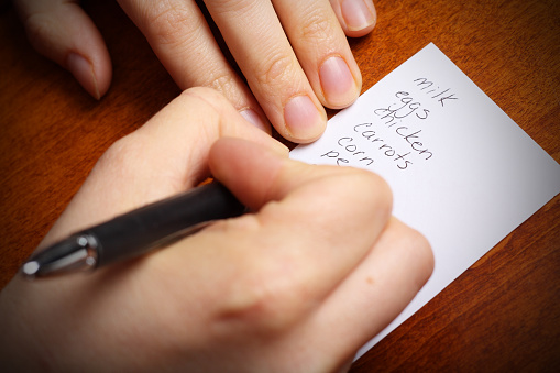 Close-up picture of person writing a grocery list that includes milk, eggs, chicken, carrots, corn, and peas