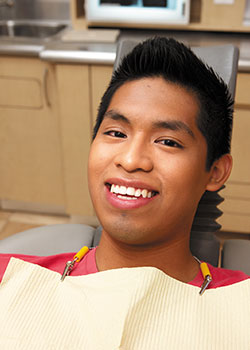 Teen boy smiling while sitting in dental chair in dentist's office