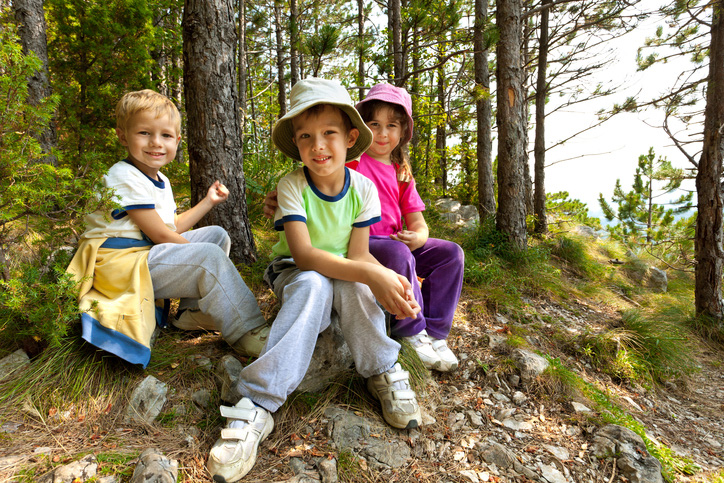 Three school age kids in a forest