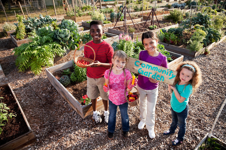 4 multi-cultural kids standing in a community garden
