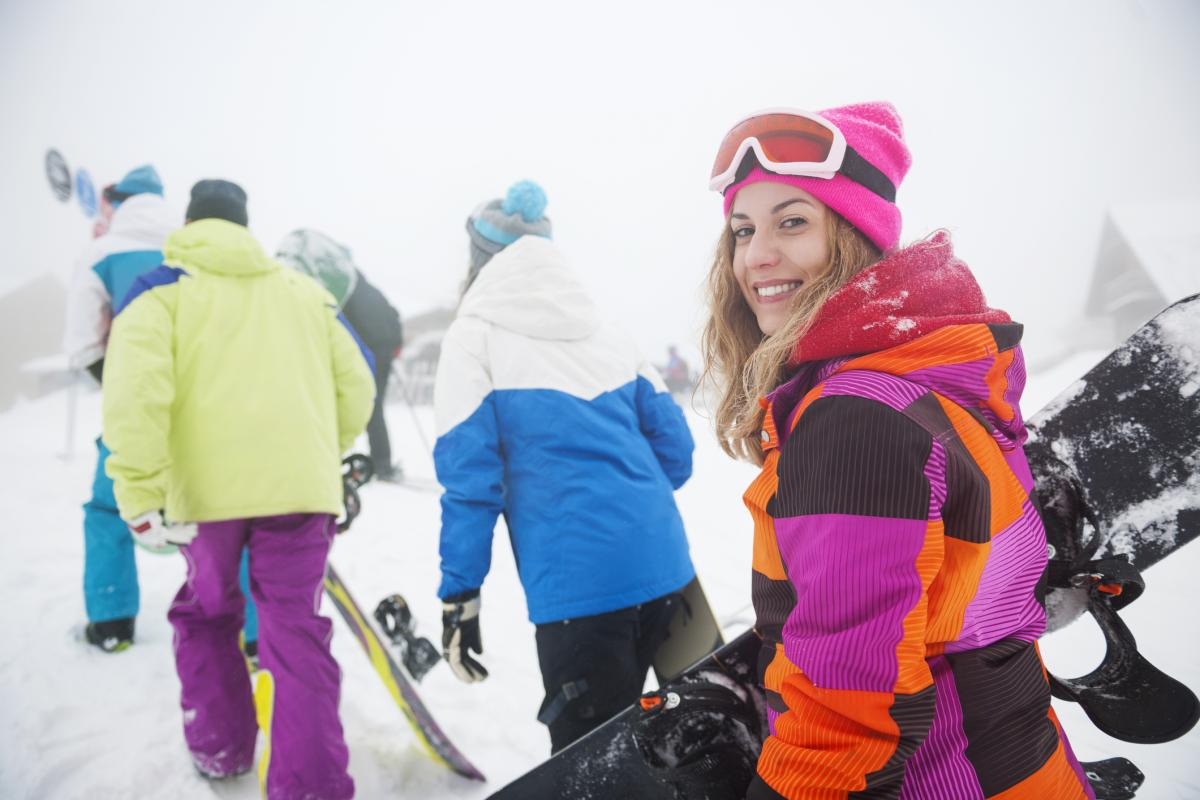 Group of adults on the mountain going snowboarding