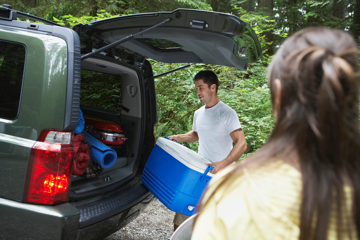 Couple loading cooler into car