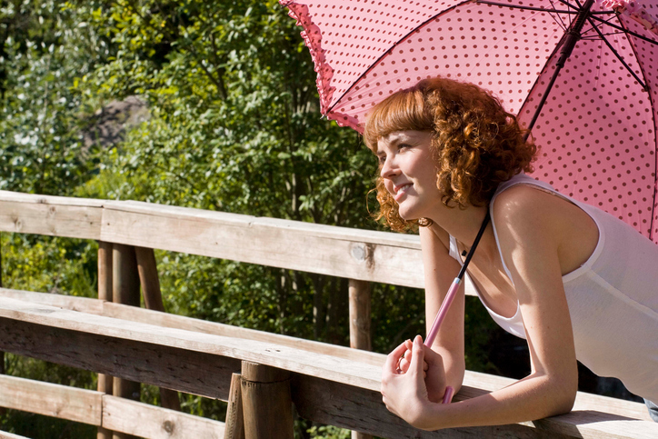 Woman leaning on rail with umbrella