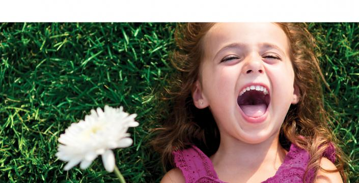 Young girl laying in the grass laughing