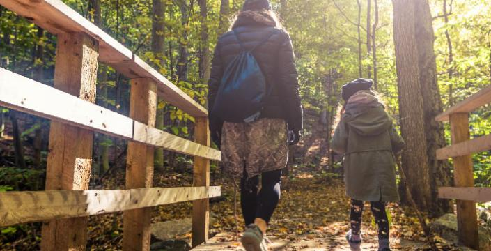 A mom and daughter hiking in the woods