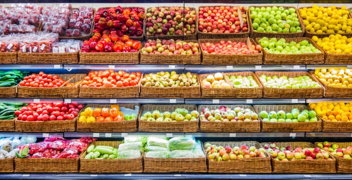 Colourful fruits and vegetables stacked decoratively in a store
