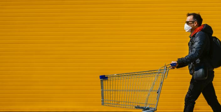 Man in mask pushing empty grocery cart