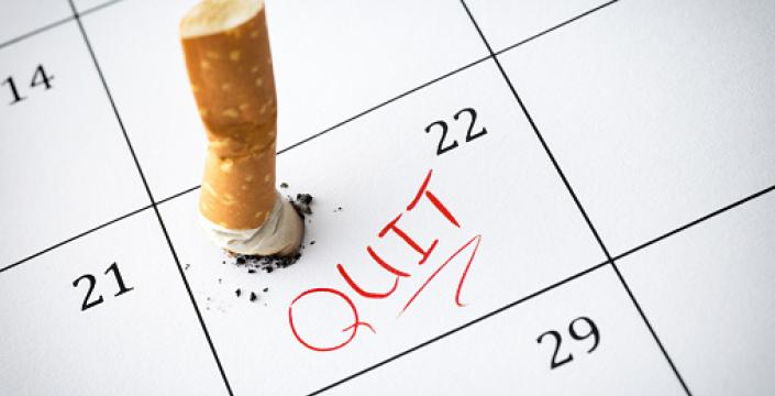Cigarette butt on calendar with the word Quit