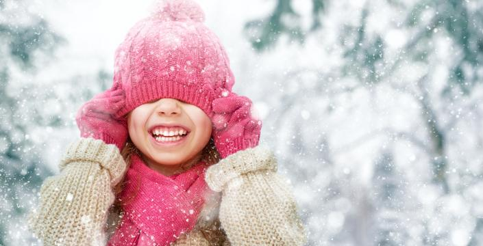 Young girl wearing winter clothes on snowy day