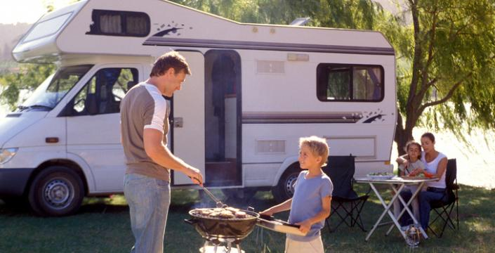 Father and son cooking at campsite
