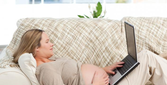 Expecting mother using computer laptop
