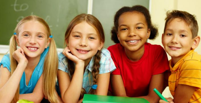 Group of children in classroom smiling