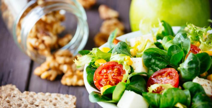 Salad, fruit and nuts on table