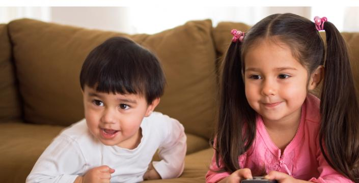 Children sitting on sofa with t.v. remote control