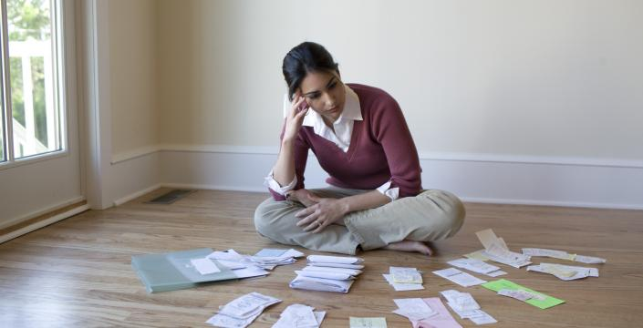 Woman sitting on floor with paperwork scattered around her