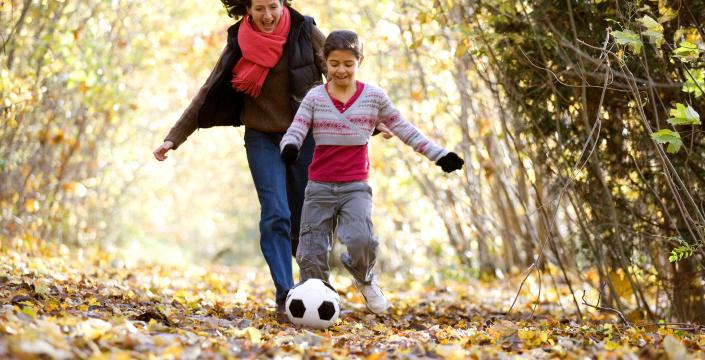 Mom and son kicking soccer ball outside in the fall