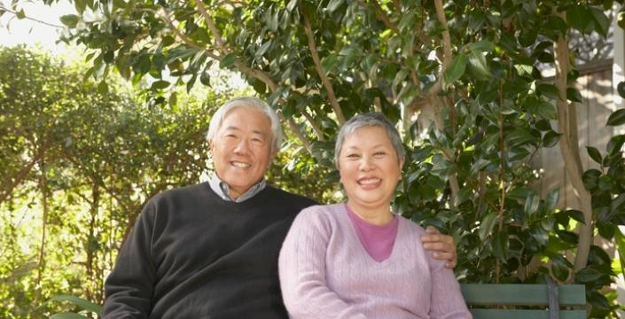 Smiling retired couple sitting on bench